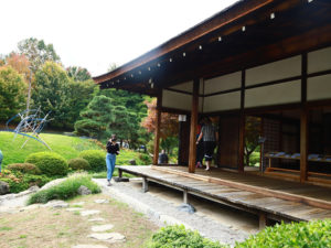 Shofuso's house, a person walking in front of it, the sun is shining.